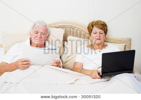 senior couple reading in bed before sleep