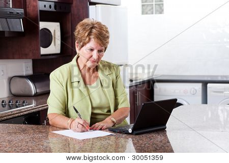 senior woman doing home finance and looks worried