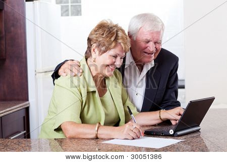 happy senior couple using internet banking checking bank balance