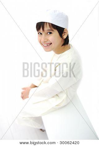 Little Arabic Muslim kid sitting indoor