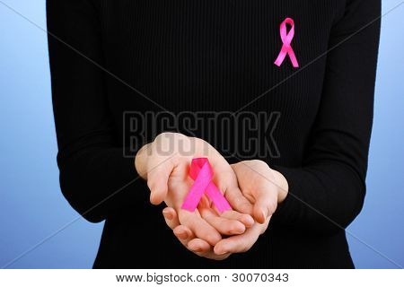 Woman with pink ribbon in hands on blue background