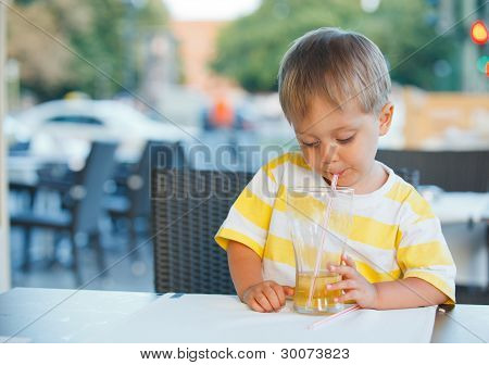 portrait of adorable little boy drinking juice