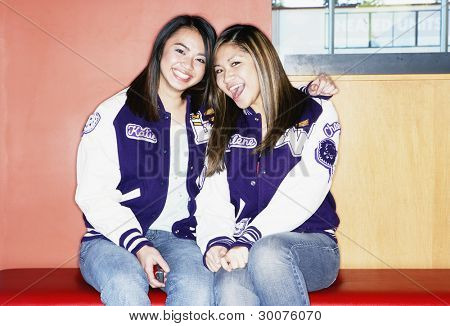 Portrait of two teenage girls wearing letterman's jackets