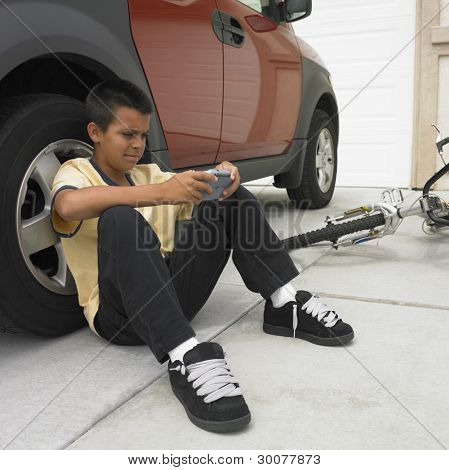Boy playing video game while leaning against vehicle