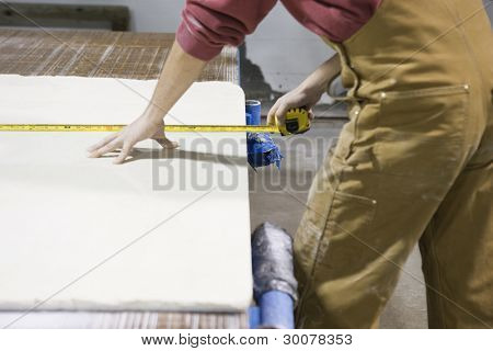 Midsection of man measuring board