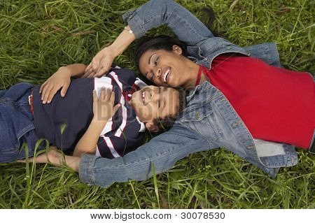 Mother and son relaxing in the grass