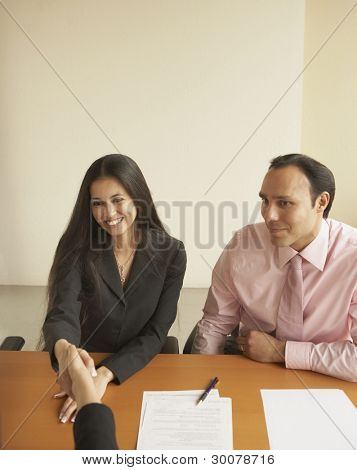 Couple shaking hands with businesswoman