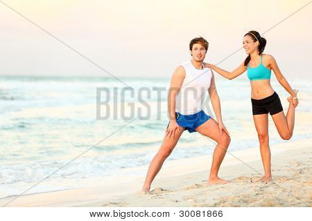 Couple doing stretching exercises workout training on beach. Young interracial running couple stretching after jogging outdoors on beautiful beach. Asian woman fitness model, Caucasian man.