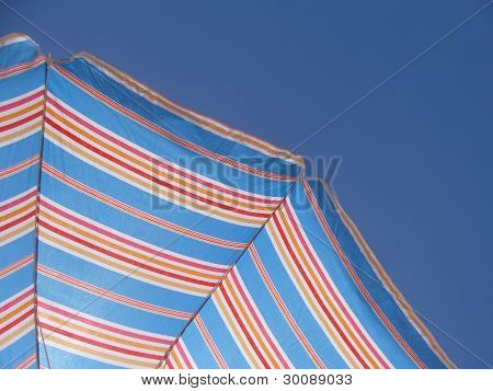 Colourful beach umbrella over a blue sky