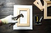 Stretching Cotton Canvas On Wooden Stretcher Bar, Canvas Pliers In A Hand poster