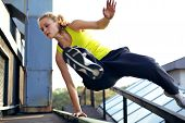 stock photo of parkour  - A woman traceur concentrating on vaulting over a railing on a high industrial building while demonstrating parkour - JPG