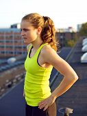image of parkour  - Beautiful young female traceur posing on an urban rooftop before participating in parkour - JPG