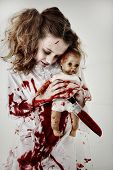 stock photo of baby doll  - Halloween Theme Girl Child Zombie or Ghost covered in blood holding knife and baby doll - JPG