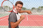 Man stood in front of tennis court holding racket over shoulder