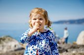 Cute Little Toddler Girl Eating Ice Cream In Cone On Family Vacations. Happy Healthy Baby Child With poster