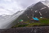 Houses In Mountains. Landscape Of Caucasus. Mountain Landscape With Haze After Rain. Light Fog Envel poster