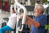 Senior Man Training On Machine At Fitness Center. High-intensity Workouts For Senior People. Sport A poster