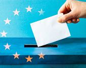 european Union parliament election concept - hand putting ballot in blue election box - EU flag poster