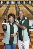 stock photo of memento  - Couple with trophy at bowling alley - JPG