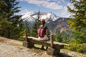 Girl Relaxing After Hike Looking To Mountain View. Traveler Sitting On Wooden Bench Enjoying Beautif poster