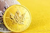 Closeup Of Silver And Golden Maple Leaf One Ounce Coins On Golden Background Placed On Left Side poster