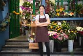 Portrait Of Smiling Owner Standing At Her Flower Shop. Young Entrepreneur Leaning With Her Arms Cros poster