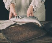 Woman In Gray Linen Clothes Holding A Fresh Sea Bass Fish Over A Brown Wooden Board, Black Backgroun poster