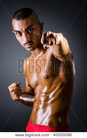 Muscular boxer in dark studio