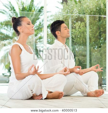 Young Couple Sitting In A Lotus Pose And Meditating