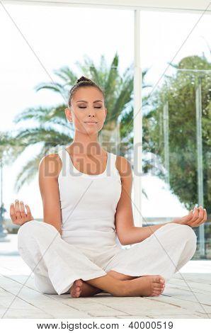 Hermosa joven haciendo Yoga en posición de loto
