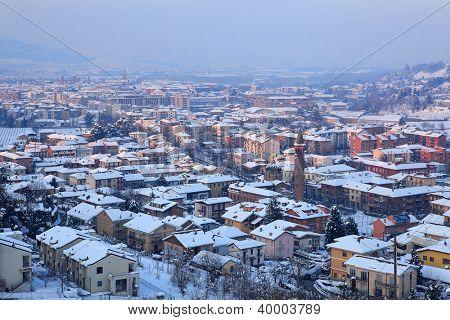 Vista aérea en la ciudad de Alba entre colinas cubiertas de nieve en la noche en el Piamonte, norte de Italia.