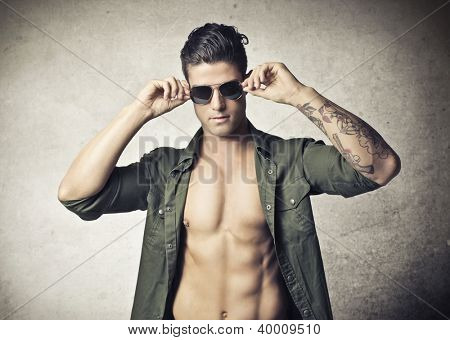 Shirtless young man with opened shirt and sunglasses