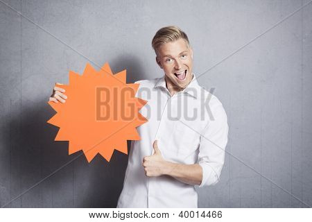 Excellent offer: Joyful salesman giving thumbs up at empty sign with space for text promoting sales isolated on grey background.