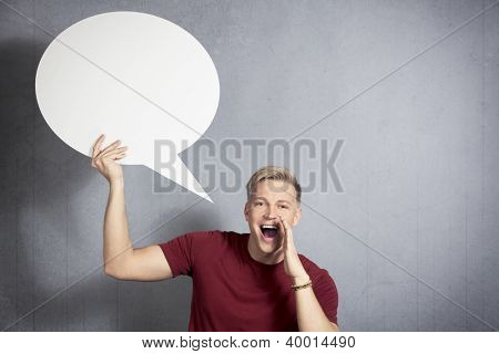 Fantastic news: Joyful man shouting great news while holding white blank speech bubble with space for text isolated on grey background.