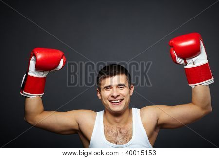 Portrait of happy young man in red boxing gloves looking at camera