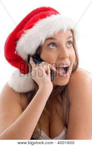 Woman Wearing Christmas Hat And Talking On Cell Phone