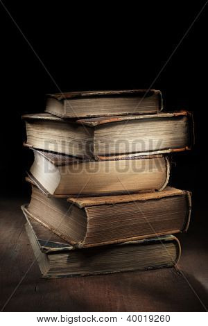 Dark and moody still life with worn and tattered old books.