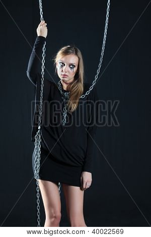 Sad zombie girl with black tears and cut throat hangs on chain at black background.