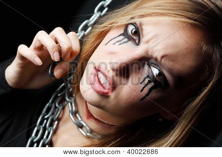 Evil zombie girl with black tears and cut throat hangs on chain at black background.