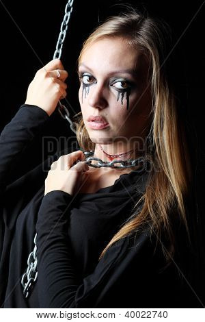 Zombie girl with black tears and cut throat clings metal chain at black background.