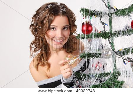 Girl in striped sweater with hair in snow touches glass ball on decorated Christmas tree.