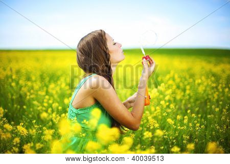 woman start soap bubbles on yellow flower field
