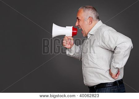 senior man shouting through the megaphone. studio shot over grey background