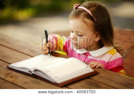 Little Girl Writes To The Notepad
