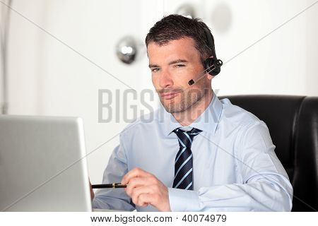 Man In Office With Laptop And Headset