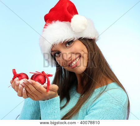 beautiful young woman holding snow with christmas balls, on blue background
