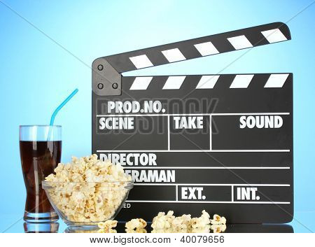 Movie clapperboard, cola and popcorn on blue background