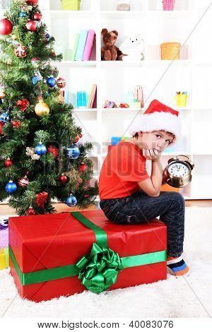 Little boy with big gift and clock in anticipation of New Year