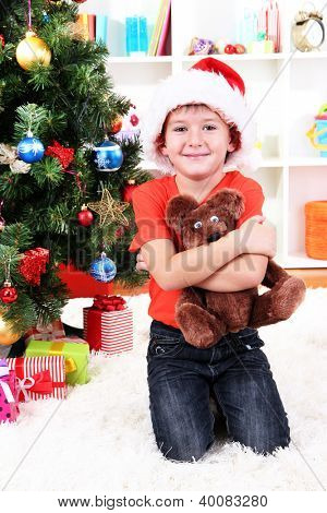 Little boy in Santa hat sits near Christmas tree with gift in hands