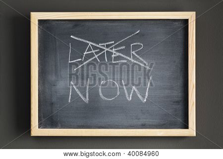 Crossing Out Later And Writing Now On A Blackboard